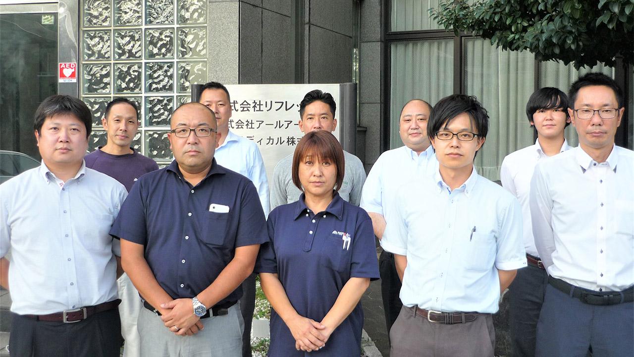 リフレックスの従業員の方が建物の前に集合され写真を撮られている様子